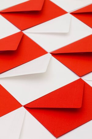 Composition with white and red envelopes on the table.