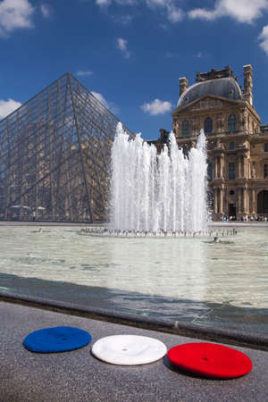 berets: Paris, France-June  17,2017: Louvre pyramid of museum  and three berets in the colors of the French flag. It is one of the worlds largest museums and a historic monument, popular landmark. Editorial