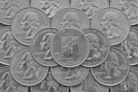 silver coins: Pile of the US quarter coins with George Washington and on the top a quarter of New Mexico State.