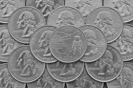 silver coins: Ohio  State and coins of USA.Pile of the US quarter coins with George Washington and on the top a quarter of Ohio State.
