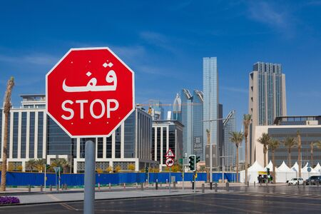 bilingual: Dubai,United Arab of  Emirates - February 7, 2012: Bilingual stop sign in Dubai with both arabic and latin writing.Typical modern architecture on a street .