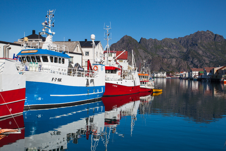 Henningsvaer, Norway - August 19,2017: Picturesque fishing port in Henningsvaer on Lofoten islands, Norway with typical red wooden buildings and small fishing boats Editorial