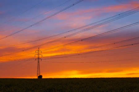 Silhouette of high voltage electrical pole structure at sunset