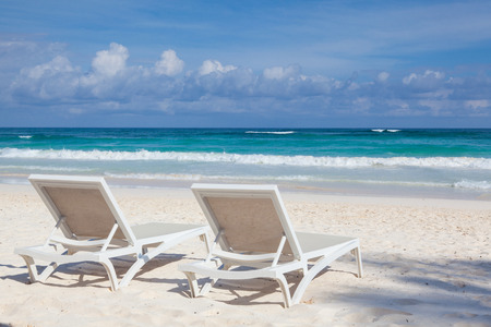 Two white beach chairs on the empty beach in Play del Carmen, Yucatan, Mexico
