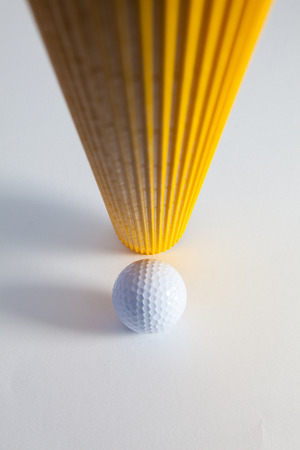 Corrugated yellow paper roll and golf ball on the white desk. Exclamation mark. Stock Photo