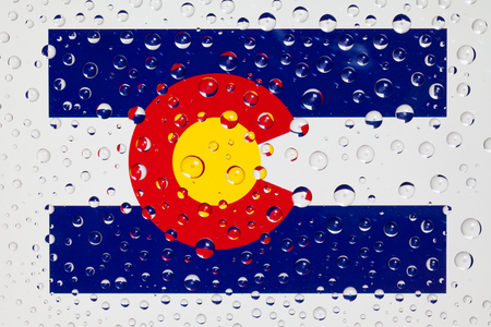 Flag of American State Colorado behind a glass covered with rain drops. Patriots day, memorial weekend, veterans day, presidents day, independence day background. Stock Photo