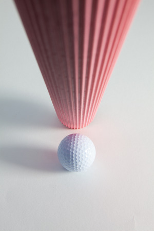 Corrugated pink paper roll and golf ball on the white desk. Exclamation mark.