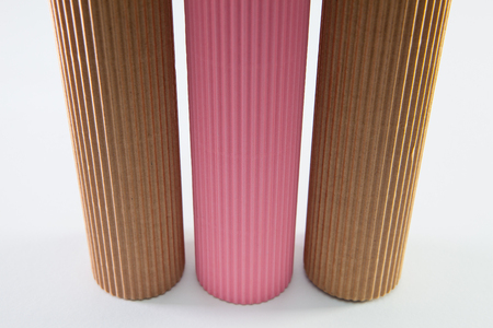 Corrugated paper rolls on the white desk. Symmetry composition.