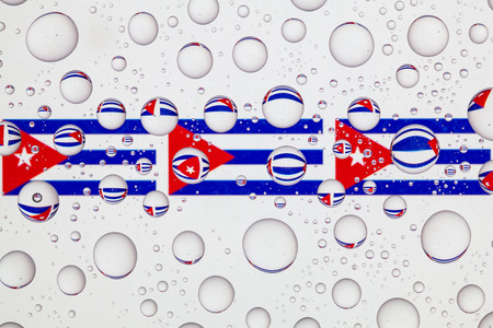 Flag of Cuba behind a glass covered with raindrops. 免版税图像