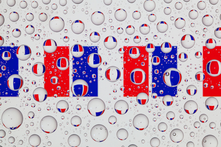 Flags  of France behind a glass covered with raindrops.