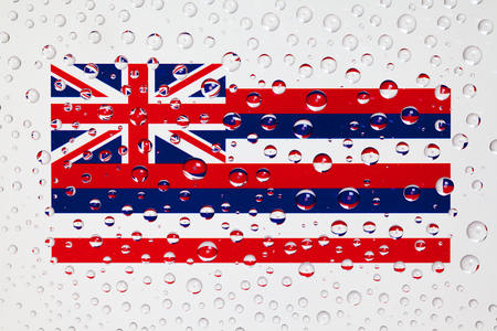 Flag of American State Hawaii behind a glass covered with rain drops. Patriots day, memorial weekend, veterans day, presidents day, independence day background.