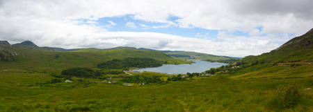 Dunlewey or Dunlewy is a small Gaeltacht village in the Gweedore area of County Donegal, Ireland. It sits in the Poisoned Glen, at the foot of Mount Errigal and on the shore of Dunlewey Lough. Stock Photo