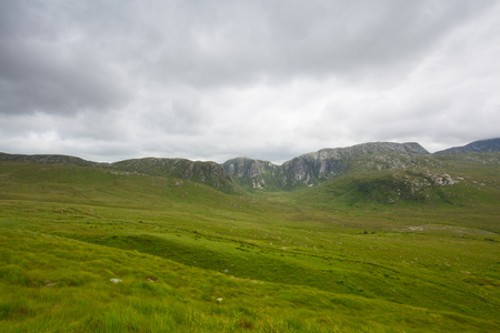Landscape in Dunlewey or Dunlewy. It is a small Gaeltacht village in the Gweedore area of County Donegal, Ireland. It sits in the Poisoned Glen, at the foot of Mount Errigal and on the shore of Dunlewey Lough.