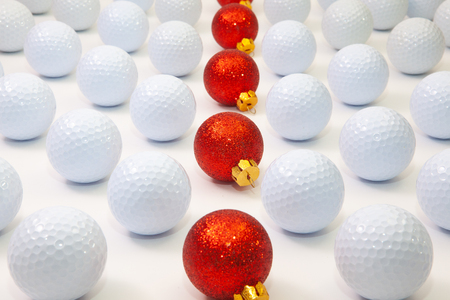 Pattern with white golf balls and red Christmas decoration on the table. 免版税图像