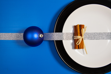 Black and white plates and Christmas decoration on the blue wooden table.Top view.Flat Lay Image.