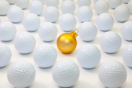 Pattern with white golf balls and gold Christmas decoration on the table. Standard-Bild