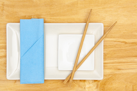 Ceramic bowls  and bamboo chopsticks for sushi food with blue napkin.