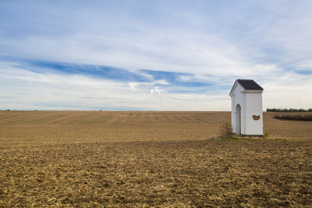 Small chapel in the autumn field. Autumn landscape with agricultural land, recently plowed and prepared for the crop.Central Bohemian Upland, Czech Republic.