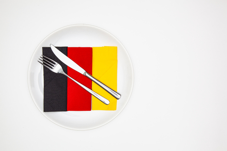 White plate and Germany flag of colorful napkins on the white wooden table.Top view. Flat Lay Image.
