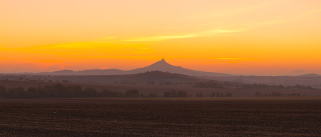 The silhouette of Hazmburk Castle at sunrise.Central Bohemian Uplands,Czech Republic. At the top of the mountain there is the ruin of a mediaeval castle, of which two towers and some wall fragments are still standing. Фото со стока