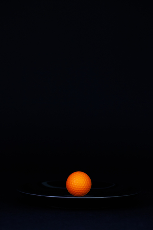 Black plate and  orange golf ball on the black background