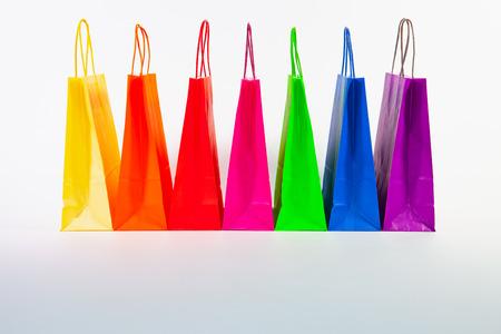 Set van kleurrijke lege boodschappentassen geïsoleerd op de witte achtergrond. Verkoop, consumentisme, reclame en retailconcept. Veel kleurrijke boodschappentassen. Stockfoto