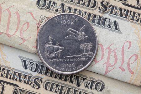 Una cuarta parte de Florida en billetes de dólares estadounidenses. Composición simétrica de billetes de dólares estadounidenses y una cuarta parte de Florida. Foto de archivo
