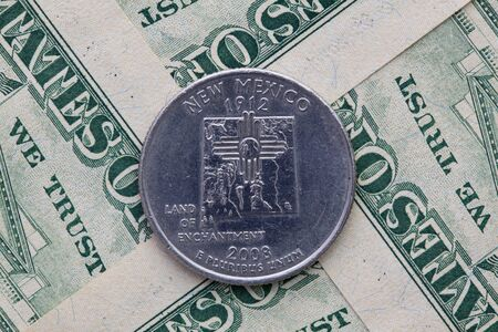 A quarter of New Mexico on US dollar bills. Symmetric composition of US dollar bills and a quarter of New Mexico.