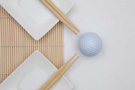 Top View Of White Empty Sushi Plates With Bamboo Chopsticks and Golf Ball. Golf  Design