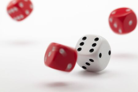 Playing dice at white wooden background. Playing a game with dice. Rolling the dice concept for business risk. Risk concept.