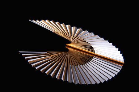 Bamboo open hand fan isolated on a black background. Traditional Japanese style luxury hand fan.