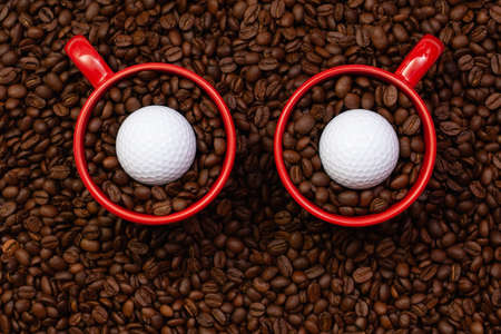Two red cups full of coffee beans and one golf ball. Fair Trade. Commodity trade. Fresh coffee beans. Funny owl.