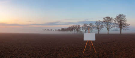 Blank art board and realistic wooden easel on the field. Landscape covered with fog in Central Bohemian Uplands, Czech Republic. Misty morning between fields.