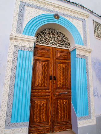 sightseers: Ornate carved wooden door surrounded by blue stinework in the medina in Kairouan Tunisia. North Africa