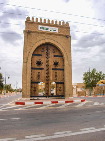 sightseers: Tall ornate carved gates by the side of the road in Tozeur Tunisia Stock Photo