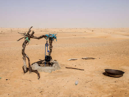 inner tube: Made from branches rope and an inner tube a single drinking well in Sahara Desert. Stock Photo
