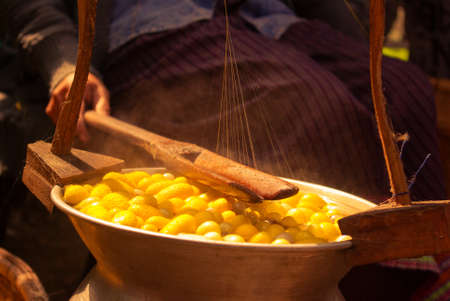 Thai woman boiling yellow silkwarm cocoons and making silk thread. A traditional way of hand made silk production.