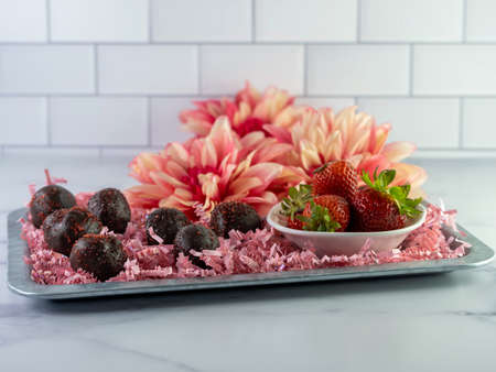 Chocolate covered Strawberry cake balls arranged on a rustic metal tray with pink paper shreds and a white bowl full of fresh strawberries and pink dahlia flowers in the background with white tile.