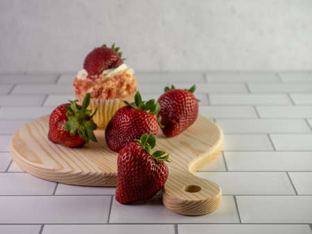Strawberry shortcake cupcake in the background with 4 strawberries in front of it, arranged on a round wooden cutting board with a handle on a white subway tile counter.