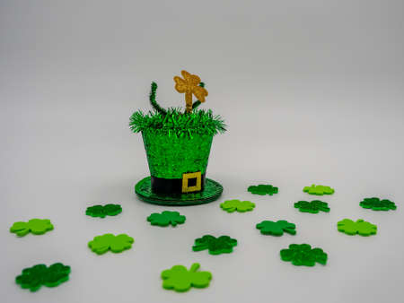 Green glittering leprechaun hat for St. Patrick's Day on a white background with little green four leaf clovers, festive for the Irish holiday!