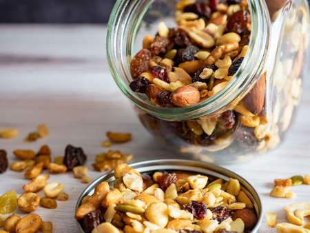 Macro Up Close Shot of a Glass Jar Filled with Seeds, Nuts and Raisins, Spilling out Onto the Lid and Counter. Healthy good fats and carbohydrates full of nutrition!