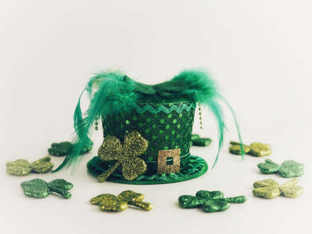 Green Leprechaun hat with polka dots and a gold buckle for St. Patrick's Day surrounded by glitter covered green four leaf clovers in a white background.