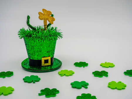 Leprechaun green glittering hat surrounded by green four leaf clovers on a white background for St. Patrick's Day.
