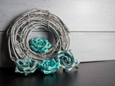 Sparkly gray nest wrapped up with teal blue paper rose flower blooms on a black slate and shiplap background.