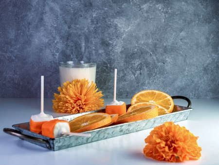 Orange Creamsicle cake pops arranged on a rustic metal tray with fresh sliced oranges and a glass of milk with orange flowers and a smoke gray background.