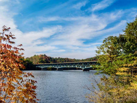 Bridge crossing over Cheat Lake in West Virginia in the fall with trees in the foreground and a bright blue and white swirly sky in the background and fall foliage trees.