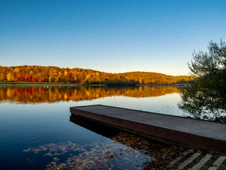 A boat dock in the foreground at Keystone Lake in West Moreland Country, nestled in the Laurel Highlands of Pennsylvania in the fall with the colorful trees reflecting in the lake and a nice blue sky.