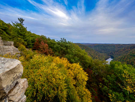 View from the top of Cooper's Rock in Coopers Rock State Forest in West Virginia right before sunset with the valley of fall colored trees below, the water running through and a beautiful blue sky