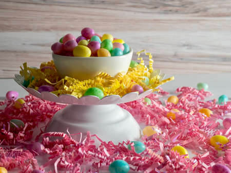 Jelly beans in a white bowl on a white platter covered with yellow paper shreds sitting on a counter atop pink paper shreds with jelly beans scattered around. Easter decor and candy.