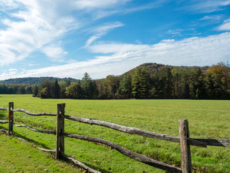Landscape nature scene in the Laurel Highlands of Pennsylvania with a fence in the foreground and a meadow and tree line in the background with bright blue cloudy skies!